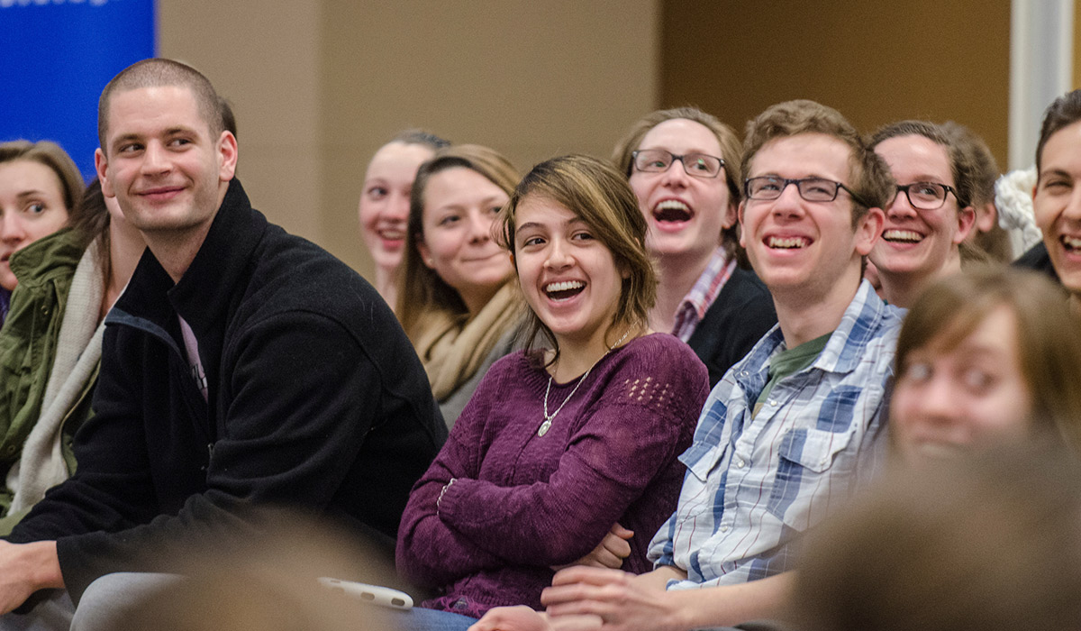 Peers students in an audience laughing